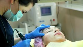 Cosmetologist in protective mask applying permanent tattooing of eyebrows in beauty salon stock image
