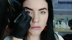 Cosmetologist pulls out eyebrows. Cosmetologist`s hand pulls out the beautiful patient`s eyebrow with a pair of tweezers. Part of the eyebrow correction stock video