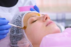 Cosmetologist puts chemical peeling of the woman`s face with brush. Cleaning the face skin and lightening freckles skin. Cosmetologist puts chemical peeling of royalty free stock photos