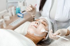 Cosmetologist puts a mask on the face. Cosmetologist uses a face mask for a young woman stock image