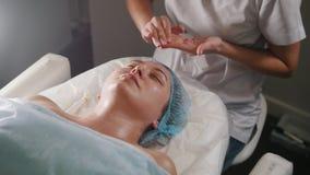 Cosmetologist que aplica el aceite en el cuello del ` s del cliente y hombros después de procedimiento cosmético almacen de metraje de vídeo