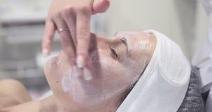 Cosmetologist que aplica la crema de cara a la mujer en el balneario almacen de metraje de vídeo