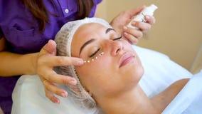 Cosmetologist que aplica la crema de piel debajo de ojos metrajes