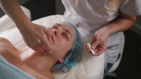 Cosmetologist que aplica la crema en la cara del ` s del cliente después de procedimiento cosmético almacen de video