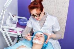 Cosmetologist que aplica la máscara en la cara imagen de archivo