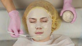 Cosmetologist que aplica a máscara facial à pele do problema jovem mulher que tem a limpeza dos procedimentos da pele 4K video estoque