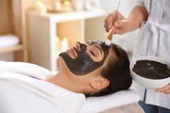 Cosmetologist que aplica a máscara preta na cara da mulher imagens de stock royalty free