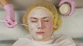 Cosmetologist que aplica a m?scara facial ? pele do problema jovem mulher que tem a limpeza dos procedimentos da pele 4K vídeos de arquivo