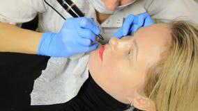 Cosmetologist que aplica maquillaje permanente Mujer hermosa joven que tiene tatuaje cosmético en sus labios Balneario sano almacen de metraje de vídeo
