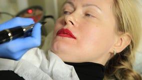 Cosmetologist que aplica maquillaje permanente Mujer hermosa joven que tiene tatuaje cosmético en sus labios Balneario sano almacen de video
