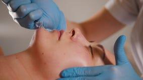 Cosmetologist que da masajes a la cara del ` s del cliente en el salón de belleza usando un aceite cosmético especial metrajes
