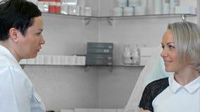 Cosmetologist que habla con el cliente femenino en la albornoz que se sienta en la oficina del cosmetologist Foto de archivo libre de regalías