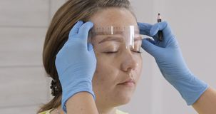 Cosmetologist que se prepara para el maquillaje permanente, tatuaje de cejas almacen de video