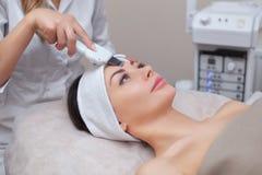 Cosmetologist robi ultradźwięk czyści procedurze twarzowa skóra piękny, młoda kobieta w piękno salonie obraz royalty free