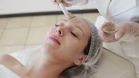 Cosmetologist setzt Maske auf Gesicht der L?genfrau in Badekurortsalon ein stock footage