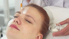 Cosmetologist smears cream on client`s forehead stock photos