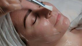Cosmetologist smeert de room op de huid van een mooi Europees meisje met een borstel Een jonge vrouw ligt met haar gesloten ogen  stock video