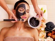 Cosmetologist smeert kosmetisch masker op het gezicht van vrouw Stock Foto