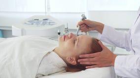 Cosmetologist som använder någon utrustning på framsida för klient` s royaltyfria bilder