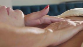 Cosmetologist som applicerar den kräm- maskeringen på framsidan av den unga härliga kvinnan lager videofilmer