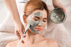 Cosmetologist som applicerar maskeringen p? kvinnas framsida, b?sta sikt royaltyfri fotografi