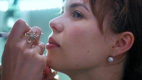 Cosmetologist som applicerar permanent makeup p? kanter arkivfilmer
