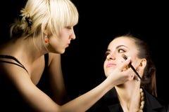 cosmetologist som gör smink Arkivfoton