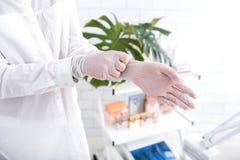 Cosmetologist som sätter på sterila handskar royaltyfri bild