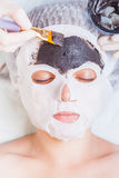 Cosmetologist in spa salon applying mud face mask using brush Royalty Free Stock Photos