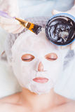 Cosmetologist in spa salon applying mud face mask using brush Stock Photography