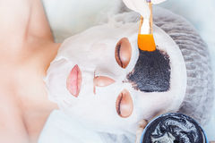 Cosmetologist in spa salon applying mud face mask using brush Stock Images