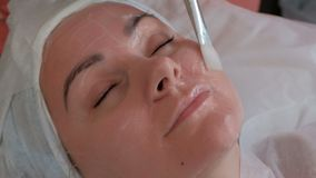 Cosmetologist stosuje białego gel czerwona twarz dziewczyna w piękno salonie z białym muśnięciem Zako?czenie zbiory wideo