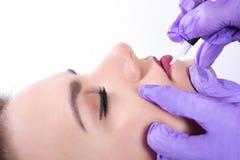 Cosmetologist stosuje stałego element uzupełniał na czerwonych wargach obraz royalty free