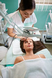 Cosmetologist treats the face of a woman looking through a magni Stock Image