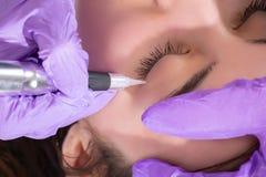 Cosmetologist treft voor het toepassen van permanente eyelinertatoegering voorbereidingen op mooi jong meisje in schoonheidsstudi royalty-vrije stock afbeelding