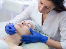 Cosmetologist tut markierendes weibliches reifes Gesicht vor Verschönerung, Abschluss oben, selektiver Fokus Schönheitschirurgiev stockfotos