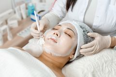 Cosmetologist puts a mask on the face. Cosmetologist uses a face mask for a young woman royalty free stock photography