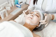 Cosmetologist puts a mask on the face. Cosmetologist uses a face mask for a young woman royalty free stock photos