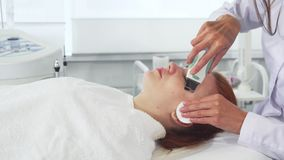 Cosmetologist uses ultrasonic machine for client`s face. Cosmetologist in white coat using ultrasonic machine for client`s face. Attractive young woman getting stock video