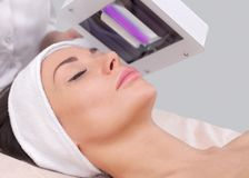 The cosmetologist uses the Wood Lamp for detailed diagnosis of the skin condition. The device detects the presence of skin diseases or inflamed areas Stock Images