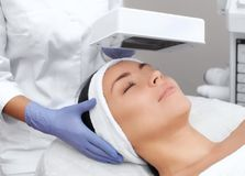 The cosmetologist uses the Wood Lamp for detailed diagnosis of the skin condition. The device detects the presence of skin diseases or inflamed areas royalty free stock image