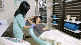 Cosmetologist veegt de geduldige oksels van ` s met katoenen spons vóór procedure af desinfectie stock video