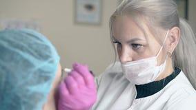 Cosmetologist wendet dauerhaftes Make-up auf Damenaugenbrauen an stock video