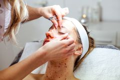 Cosmetologist woman is doing eyebrow modeling for woman / girl by wax for epilation. Cosmetological clinic. Healthcare. Cosmetologist women is doing eyebrow Royalty Free Stock Images