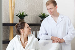 Cosmetologist and woman talking at spa salon Stock Image
