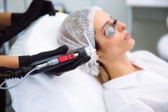 Cosmetologist womanClose-up Cosmetologist делает обработку к стороне молодой женщины, процедуры по лазера epilation удаления воло стоковые фото