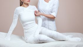The cosmetologist wraps the leg of the customer. Anti-cellulite procedure-STYX wrap royalty free stock photos
