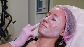 Cosmetologist zet op een masker stock video