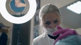 Cosmetologistbesprekingen met cliënt over brows in schoonheidskliniek stock footage