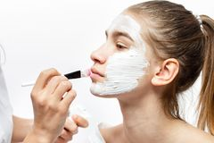 Cosmetologisten applicerar med en vit kosmetisk maskering f?r borste p? framsidan av den unga brunh?riga flickan royaltyfria bilder